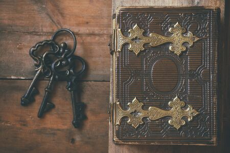 clasps: top view of antique book cover, with brass clasps and old keys. vintage filtered and toned. selective focus
