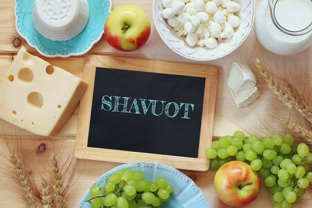 image of dairy products and fruits next to blackboard with the phrase: SHAVUOT, on wooden background.