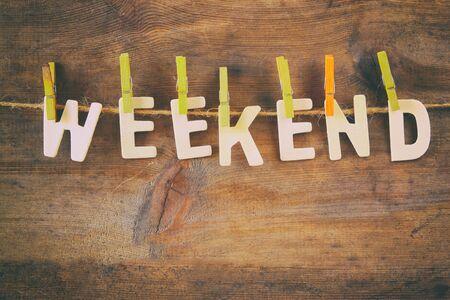 fin de semana: La palabra WEEKEND hecha de letras de madera que cuelgan en la cuerda sobre fondo rústico. Retro filtrado