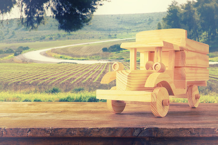 nostalgia: old wooden toy car over wooden table. nostalgia and simplicity concept. vintage style image