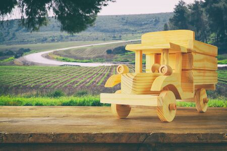 wooden toy: old wooden toy car over wooden table. nostalgia and simplicity concept. vintage style image