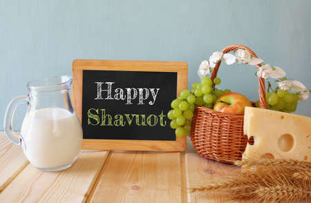 image of dairy products and fruits next to blackboard, on wooden background. Symbols of jewish holiday - Shavuot