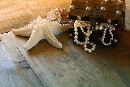 perl: image of white pearls necklace in treasure chest next to seashells on old grunge wooden table. vintage filtered and toned