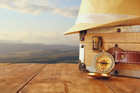 traveler vintage luggage, compass and fedora hat on wooden table. explorer and adventure concept. vintage filtered image Archivio Fotografico