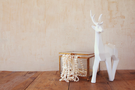 perl: image of white pearls necklace and white deer on old grunge wooden table. vintage filtered