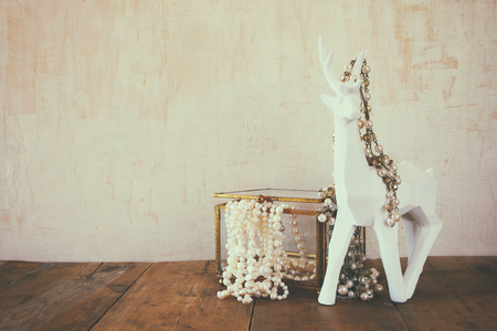 jewelries: image of white pearls necklace and white deer on old grunge wooden table. vintage filtered and toned