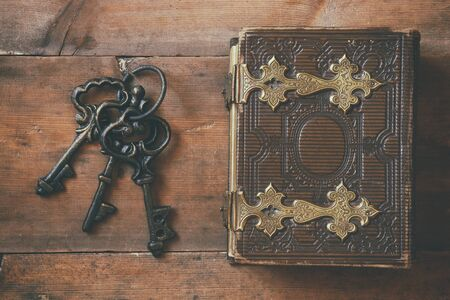 clasps: top view of antique book cover, with brass clasps and old keys. vintage filtered and toned