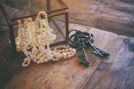 perl: image of white pearls necklace on old grunge wooden table. vintage filtered and toned Stock Photo