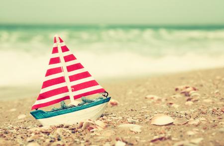 nautic: sailboat on sea sand and ocean horizon. vintage filtered Stock Photo