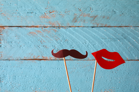 paper heart shape fake lips and mustaches in sticks in front of wooden background. vintage filtered image