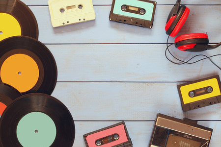 tape player: top view image of cassette, headphones, records and old tape player over wooden background. vintage filter Stock Photo