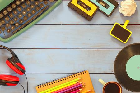 image vue de dessus des objets de style eightees sur une table en bois. cassettes de machine à écrire, disque et casque.