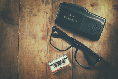 tape recorder: top view image of investigation concept. tape recorder, cassete and glasses. vintage filtered and toned