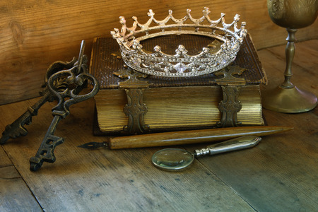 low key image of beautiful diamond queen crown on old book. vintage filtered. fantasy middle age concept