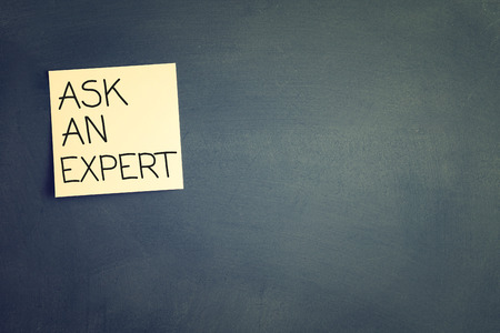 warranty questions: sticky with the note ask an expert over chalkboard. room for text Stock Photo