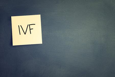 vitro: sticky with the note IVF (In Vitro Fertilization) over chalkboard. room for text Foto de archivo