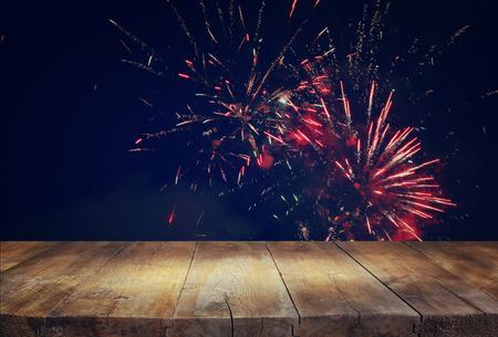 julio: Imagen de la mesa de madera delante de fondo de fuegos artificiales borrosa
