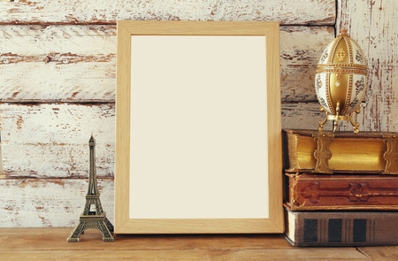 empty table: image of blank wooden frame, next to old books. template, ready to put photography. vintage filtered Stock Photo