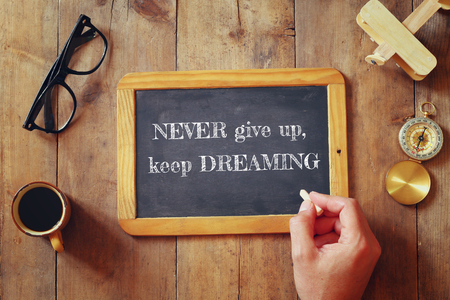 give up: man writes on a blackboard a phrase: NEVER GIVE UP, KEEP DREAMING. Positive  motivational quote message. Top view. vintage style image