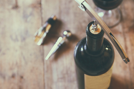 top view image of red wine bottle and corkscrew over wooden table. retro style image selective focus.
