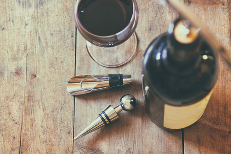 bar top: top view image of red wine bottle and corkscrew over wooden table. retro style image selective focus.