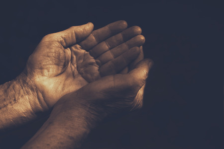 honour: male Wrinkled old hands begging asking for money, help, reaching out and compassion concept