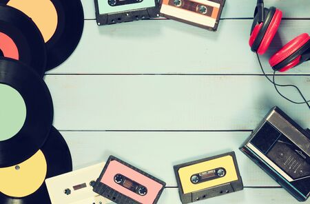 tape player: top view image of cassette, headphones, records and old tape player over wooden background. retro filter
