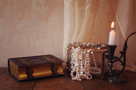 burning time: low key image of  white pearls next to old book. vintage filtered. fantasy middle age concept