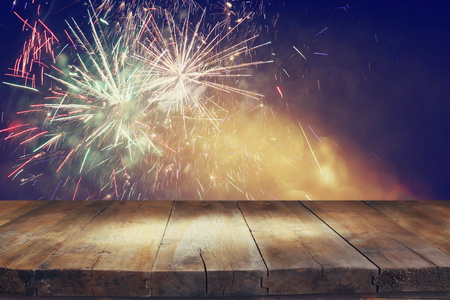 top of the year: image of wooden table in front of blurred fireworks background