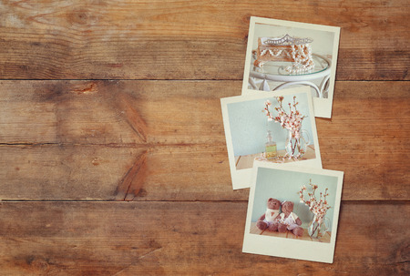 vintage objects: top view of instant polaroid photos album on wooden background. vintage filtered image Stock Photo