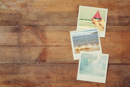 top view of instant photos album on wooden background. vintage filtered image Stok Fotoğraf