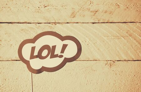 laugh out loud: LOL bubble text comic retro sign, in front of wooden background. sepia style filter