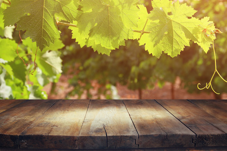 image of wooden table in front of Vineyard landscape. vintage filtered