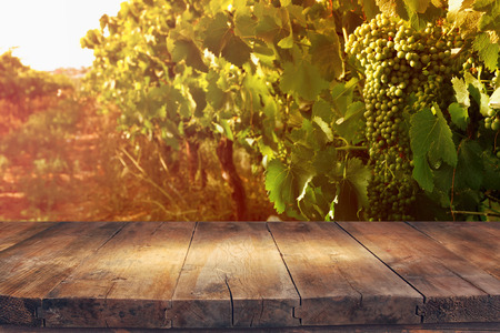 image of wooden table in front of Vineyard landscape at sunset light. vintage filtered Stock Photo