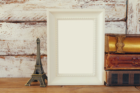 fashion art: image of blank wooden frame, next to old books. template, ready to put photography. vintage filtered Stock Photo