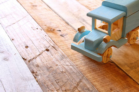 old wooden toy car over wooden table. nostalgia and simplicity concept. vintage style image