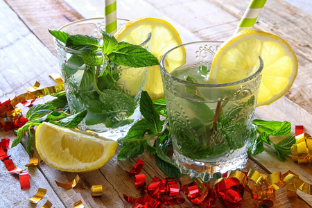 citrus: fresh mojito and sliced lemons on a rustic wooden table