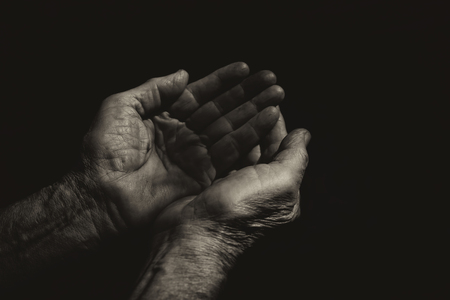 hungry: low key image of male Wrinkled old hands begging asking for money, help, reaching out and compassion concept. black and white photo