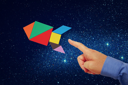 missed: mans hand pointing at rocket made from square tangram puzzle, abstract space background