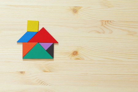 house made from tangram puzzle over wooden table. retro style image
