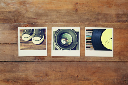 top view of instant photos album on wooden background. vintage filtered