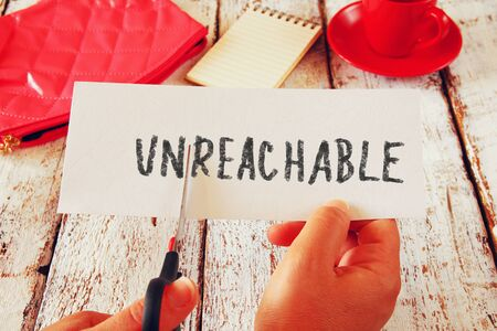 unreachable: woman hand holding card with the text unreachable, cutting the word unso it written reachable. success and challenge concept. retro style