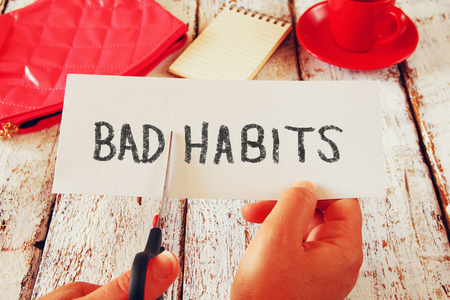 self dependent: woman hand holding card with the text bad habits, cutting the word bad so it written habits. success and challenge concept. retro style