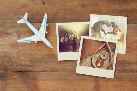 plane table: top view of travel instant photographs next to airplane over wooden table. traveling concept. top view