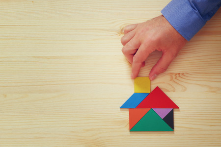 mans hand pointing at house made from tangram puzzle over wooden table Stock Photo