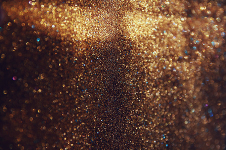 glitter vintage lights background. gold, black. defocused.