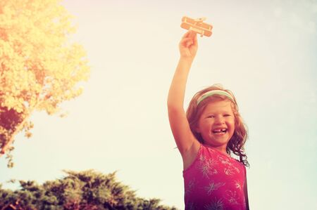 vintage photo: cute little girl holding wooden toy airplane against the sky. retro filtered image