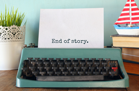 photo of vintage typewriter with phrase: END OF STORY, on wooden table Stockfoto