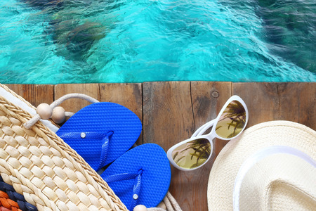 top view of sea and wooden deck with beach accessories Stock Photo