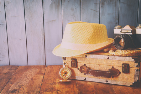 old items: Compass, rope, old camera and fedora hat over wooden table. explorer and adventure concept. retro filtered and toned image Stock Photo